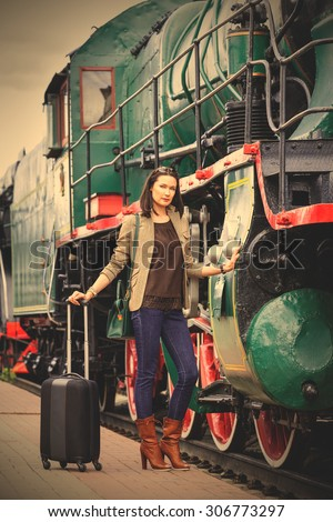 beautiful middle-aged women in retro style travel. she is near ancient train on station platform. instagram image filter retro style - stock photo