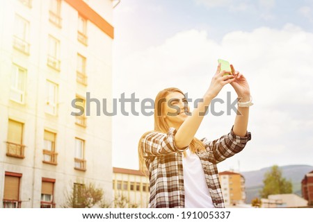 Beautiful millennial hipster young Caucasian woman taking a selfie with smart phone outdoors on sunny summer day. Urban scene background. Casual fashionable style clothes. Modern lifestyle concept. - stock photo
