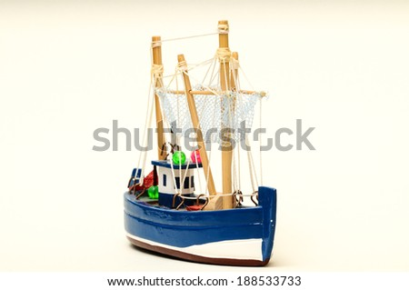 Beautiful miniature ship. Wooden sailship figurine. Antique model sailing boat isolated on white - stock photo
