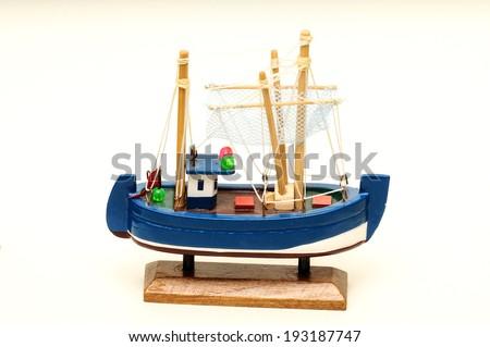 Beautiful miniature ship. Wooden sailship figurine. Antique model sailing boat isolated on white - stock photo