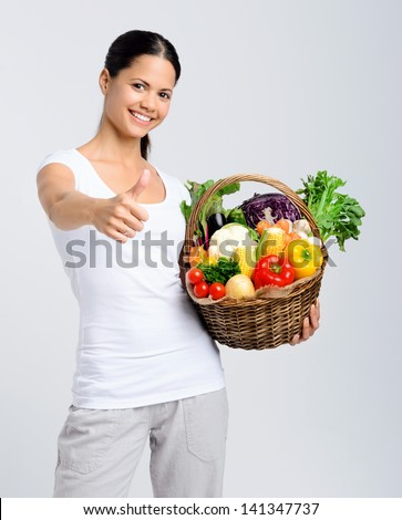Beautiful mix race woman smiling and holding a basket full of fresh organic vegetables and giving a thumbs up - stock photo