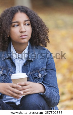 Beautiful mixed race African American girl teenager female young woman drinking takeaway coffee outside sitting in a park in autumn or fall looking sad depressed or thoughtful - stock photo