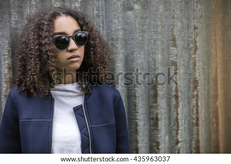 Beautiful mixed race African American girl teenager female young woman outside wearing sunglasses looking sad depressed or thoughtful - stock photo