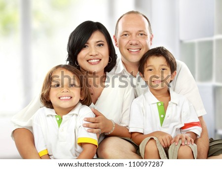 Beautiful mixed race family in the living room - stock photo