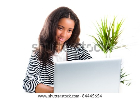 Beautiful mixed race teen girl, working on a laptop with an admiring glance - isolated on white - with a plant - stock photo