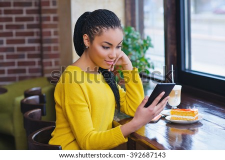 Beautiful mixed race teenage girl using digital tablet and enjoying her coffee break  - stock photo
