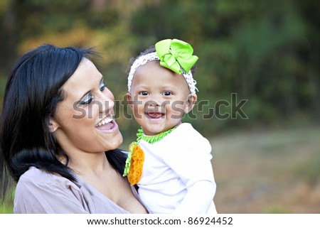 Beautiful mixed race young mother and baby daughter laughing and having fun together - stock photo