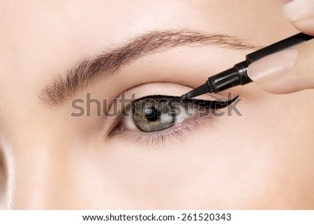 Beautiful model applying eyeliner closeup on eye - stock photo