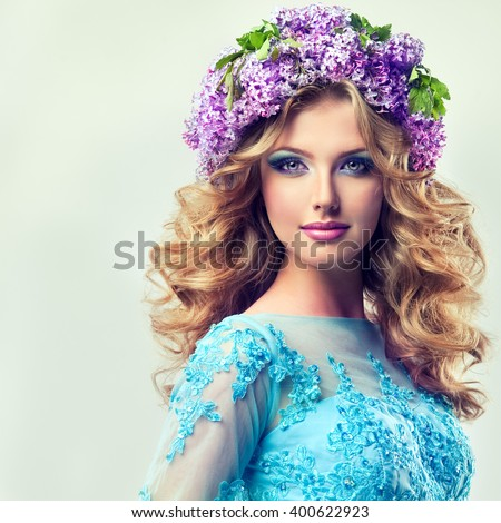 Beautiful model blonde girl   of flowers lilac  on the head    ,with curly long hair.  Girl spring . Summer image .Makeup,cosmetics,beauty. wreath of lilac on the head . - stock photo
