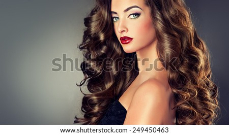 Beautiful model brunette with long curled hair - stock photo