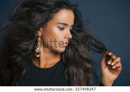 Beautiful model brunette with long curled hair. Profile side. Purple eyeshadow. Pink Lipstick and jewelry earrings. Studio shot over blue background. Horizontal - stock photo