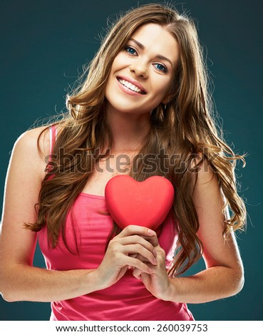 Beautiful model. Close up face portrait of smiling woman holding red heart. Female model with long hair. - stock photo