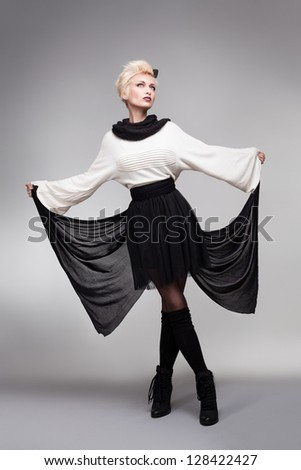 beautiful model holding her dress like a butterfly wing on gray background - stock photo
