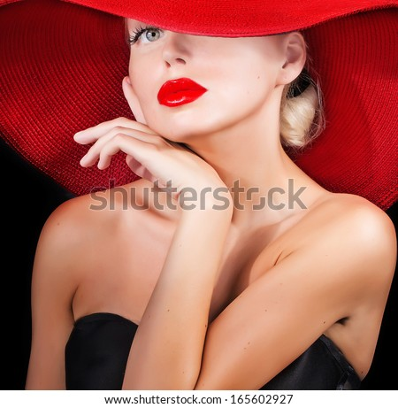 beautiful model  in red hat with red lips looking at camera - stock photo