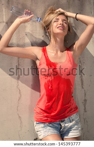 Beautiful model relax at the wall with a bottle of water - stock photo