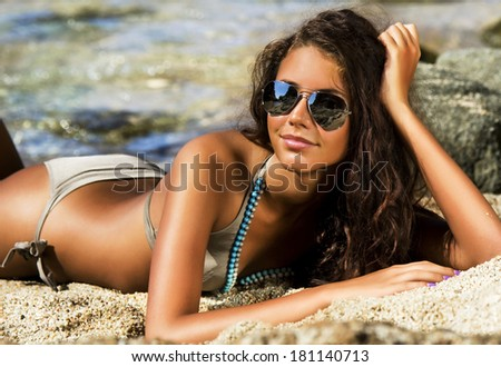 Beautiful model relaxing on a beach. - stock photo