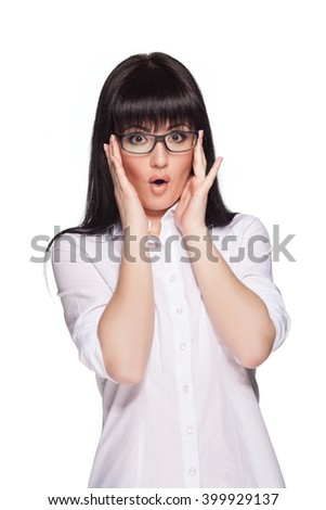 Beautiful model wearing glasses and a white office shirt. Pretty brunette is very surprised. - stock photo