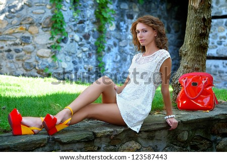Beautiful model with a short white dress and red and yellow heels - stock photo