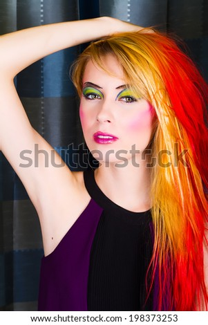 Beautiful Model with Colorful Makeup Playing With Her Long Blonde and Red Hair - stock photo