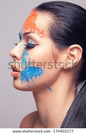 beautiful model with dry colored powder - stock photo