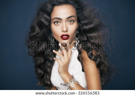 Beautiful model with elegant hairstyle and glamorous jewelry . Attractive woman with fashion wavy hairstyle and colourful makeup over blue background. Studio shot, Horizontal - stock photo
