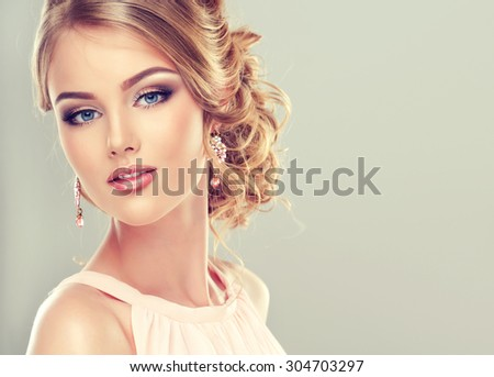 Beautiful model with  elegant hairstyle . Beautiful woman with fashion wedding hairstyle and colourful makeup - stock photo