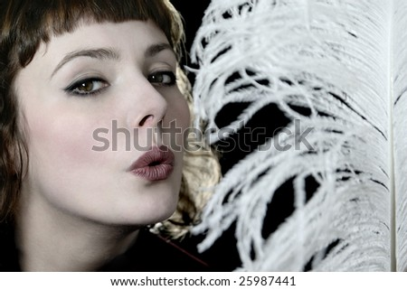 Beautiful model with feather. - stock photo