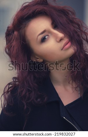 Beautiful model with long curly brunette hair outdoors - stock photo