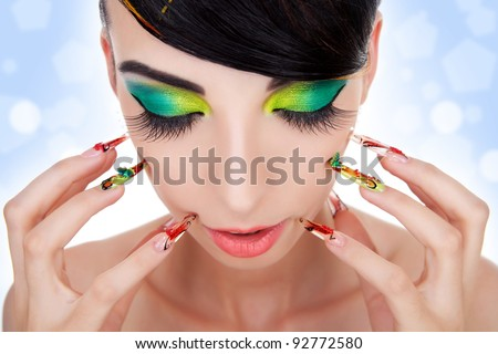 Beautiful model with long fingernails against face and looking down. Luxury fashion style, manicure, cosmetics and make-up. portrait of female model with red lipstick, fingernails and clean skin - stock photo