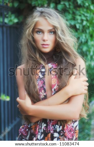 Beautiful model with long hair on natural background - stock photo