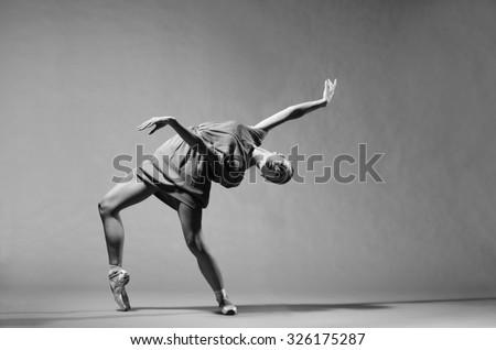 Beautiful modern ballet dancer on tiptoe posing in studio. Extreme flexibility. - stock photo