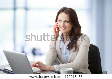 Beautiful modern businesswoman working on her laptop in office and having a phone conversation.  - stock photo