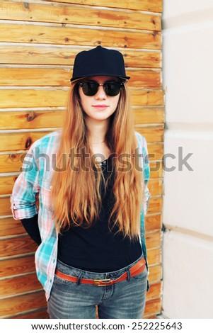 Beautiful modern girl near the wooden and brick wall. Youth style. Fashion shot. - stock photo