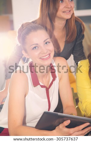 Beautiful modern student woman holding tablet computer with colleague on background. Young woman using tablet in business training. Cheerful group of students or colleagues in the room school office. - stock photo