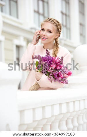 Beautiful modern young woman in springtime. Woman with bouquet of tulips and lilac. Smiling woman talking on the phone and looking away - stock photo