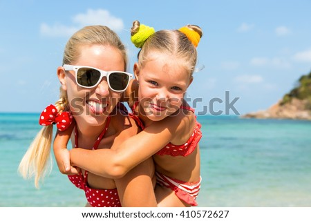 Beautiful mom sunglasses with cute little daughter on her back. Two in red bikini. Woman and little girl show tongue, smile and looking to camera. Happy family on the sea shore. Happy mothers day. - stock photo
