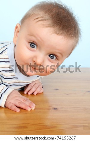 Beautiful 6 month old baby boy against blue background - stock photo