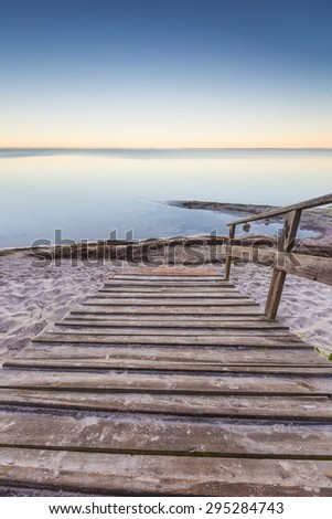 Beautiful morning landscape with wooden stairs leading to the sea. Landscape of beach in Jastarnia, Poland. - stock photo