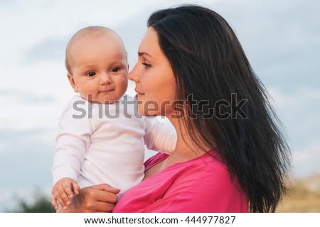 Beautiful Mother And Baby outdoors. Beauty Mum and her Child playing in Park together. Outdoor Portrait of happy family - stock photo