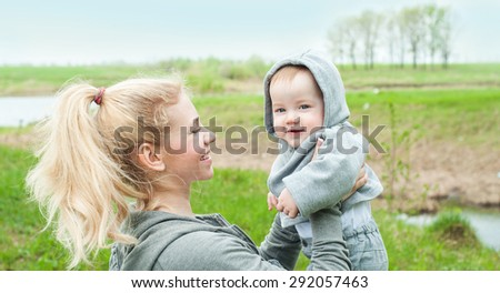Beautiful Mother And Baby outdoors. Nature. Mum and her Child playing in Park together. Happy family. - stock photo