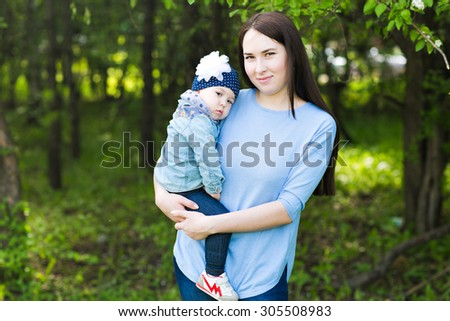 Beautiful Mother And Baby outdoors. Nature. Outdoor Portrait of happy family.  Mom and Baby - stock photo