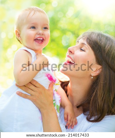 Beautiful Mother And Baby playing in a park. outdoors. Nature. Beauty Mum and her Child playing outdoors together. Outdoor Portrait of happy family. Joy. Mom and Baby  - stock photo