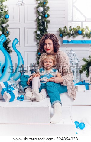 beautiful mother and charming daughter, sitting next to a Christmas tree and Christmas balls in warm stylish sweater and jeans, with depth of field Photo - stock photo
