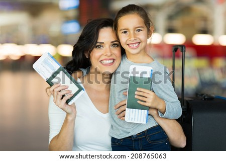beautiful mother and daughter holding passports and boarding pass at airport - stock photo