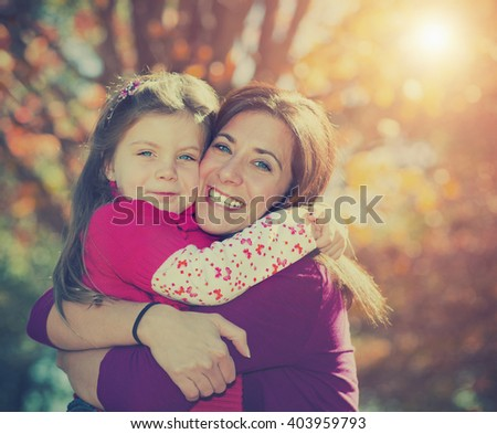 Beautiful mother and daughter hugging against fall background with instagram style filter - stock photo