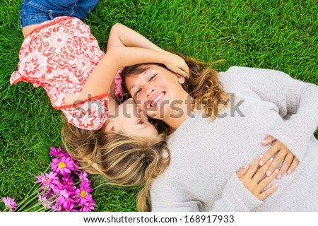Beautiful mother and daughter lying together outside on grass, Happy intimate moment, Cute little girl snuggling her mom - stock photo
