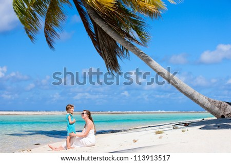 Beautiful mother and daughter on a deserted tropical beach - stock photo
