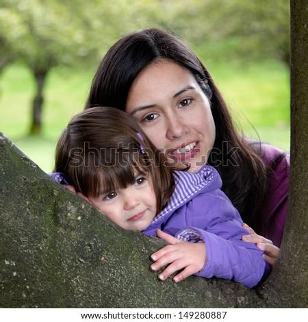 Beautiful Mother and Daughter Resting on a Tree as they Enjoy Nature - stock photo