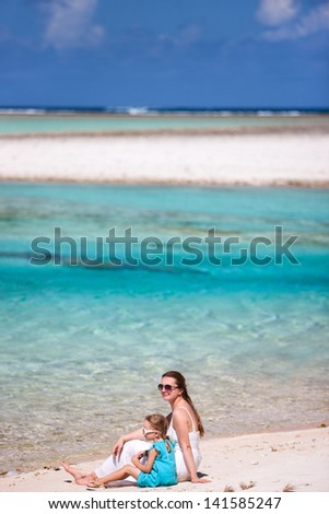 Beautiful mother and daughter sitting on a deserted tropical beach - stock photo