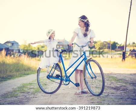 Beautiful mother and daughter traveling on a bicycle. - stock photo